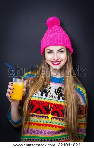 Closeup portrait of happy gorgeous fashionable young woman wearing trendy colorful winter outfit. Teenage girl in vibrant sweater and pink knitted hat holding jar of juice. Black background, Retouched - stock photo