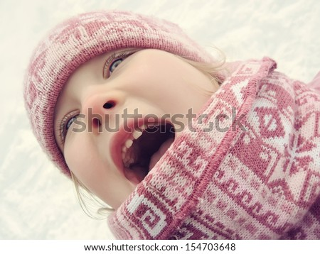 Closeup portrait of happy little girl is laughing in winter