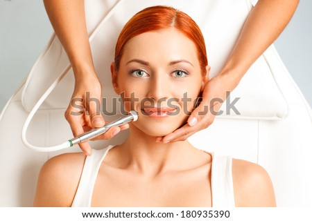 closeup portrait of happy redheaded woman getting microdermabrasion procedure in a beauty salon - stock photo