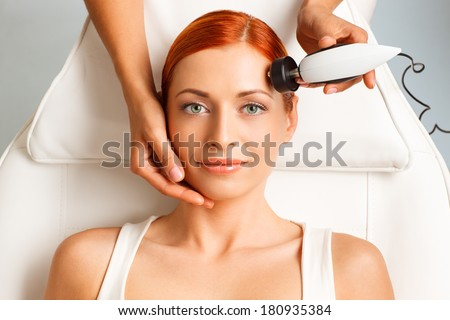closeup portrait of happy redheaded woman getting rf-lifting in a beauty salon