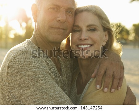 Closeup portrait of happy senior couple embracing on tropical beach - stock photo