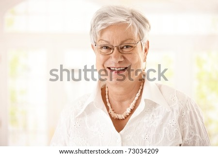 Closeup portrait of happy senior woman with glasses, looking at camera, smiling.? - stock photo
