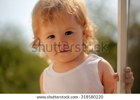 Closeup portrait of happy smiling cute little boy with blond curly hair in white underwear looking forward standing outdoor sunny day on natural background, horizontal picture