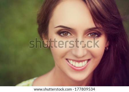 Closeup Portrait of Happy Smiling Woman on Summer Nature Background. Toned Photo. Shallow Depth of Field. - stock photo