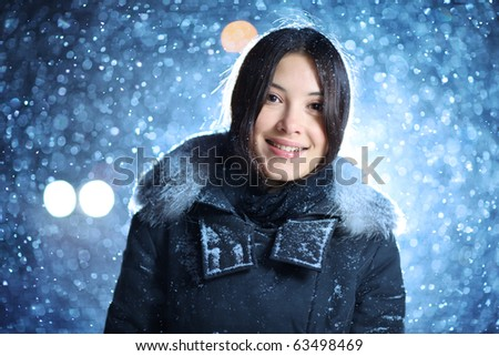 Closeup portrait of happy smiling young female in winter clothes over falling snow background at night.