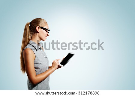 Closeup portrait of happy young blonde business woman using tablet pc isolated on blue background. Side view of a smiling girl holding a digital tablet computer. - stock photo
