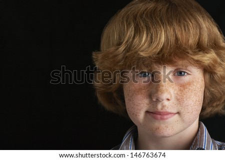 Closeup portrait of happy young boy isolated on black background - stock photo