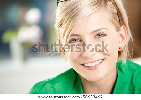 Closeup portrait of happy young businesswoman wearing green shirt, smiling.
