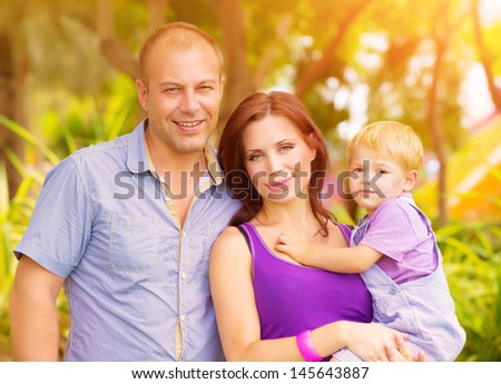 Closeup portrait of happy young family having fun outdoors, cheerful parents with adorable kid walking in the park, summer vacation