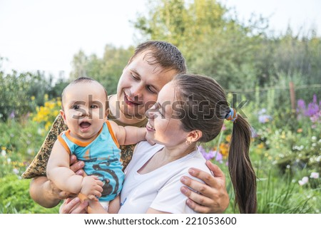 Closeup portrait of happy young family having fun outdoors, cheerful parents with adorable kid walking in the park, summer vacation Baby boy looking at camera Empty copy space for inscription