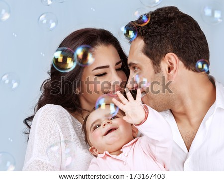 Closeup portrait of happy young family playing with soap bubbles isolated on blue background, having fun, playing game, happiness and joy concept