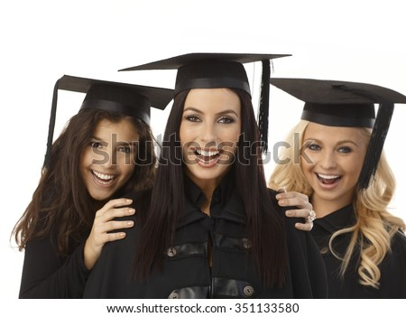 Closeup portrait of happy young female graduates in academic dress and square academic cap hugging.  .