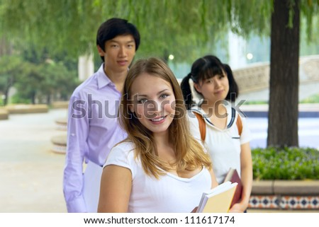 Closeup portrait of happy young girls and boy. Students outside school holding books. Group of people looking smiling together. American and Asian teenagers studying outside of university campus. - stock photo