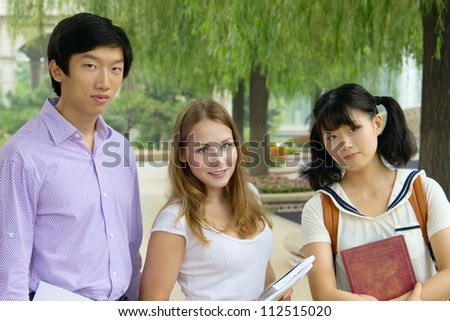 Closeup portrait of happy young girls and boy. Students outside school holding books. Group of people looking smiling together - stock photo
