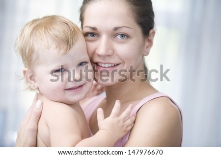 Closeup portrait of happy young mother cuddling baby girl