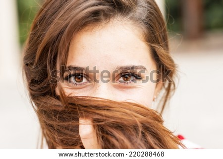 Closeup portrait of happy young woman covers her face of hair. - stock photo
