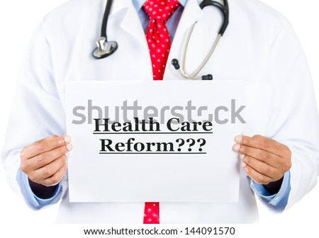 """Closeup portrait of health care professional with red tie and stethoscope holding up a sign which says """"Health Care Reform???"""", isolated on white background - stock photo"""
