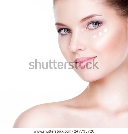Closeup portrait of healthy beautiful woman with cosmetic cream under the eyes - isolated on white. - stock photo