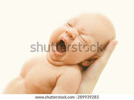 Closeup portrait of infant yawning on hands mother