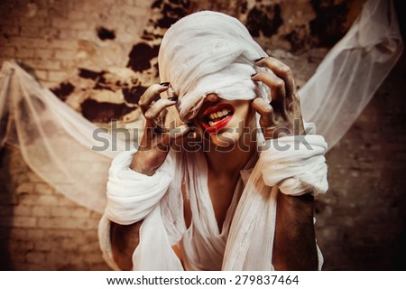 Closeup portrait of insane creature scratching her closed by bandage drawn face and red lips at bricks wall background. - stock photo