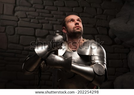 Closeup portrait of inspired medieval knight looking up and kneeling with sword on a dark stonewall background
