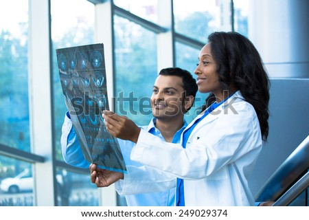Closeup portrait of intellectual healthcare professionals with white labcoat, looking at full body x-ray radiographic image, ct scan, mri, isolated hospital clinic background. Radiology department - stock photo