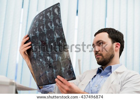 Closeup portrait of intellectual man healthcare personnel with white labcoat, looking at brain x-ray radiographic image, ct scan, mri, clinic office background. Radiology department