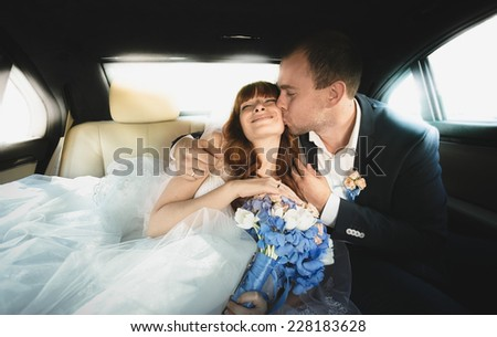 Closeup portrait of just married couple hugging on car backseat - stock photo