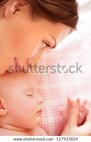 Closeup portrait of little adorable child sleeping with beautiful young mother, resting at home, loving family, tenderness concept - stock photo