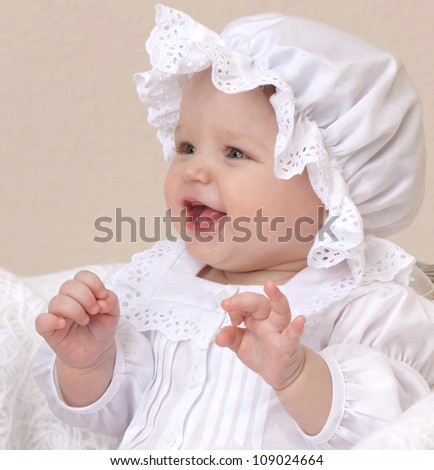 closeup portrait of little child baby girl  smiling in white clothing hat - stock photo