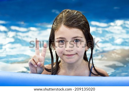 Closeup portrait of little girl in pool. Is fingers V - stock photo