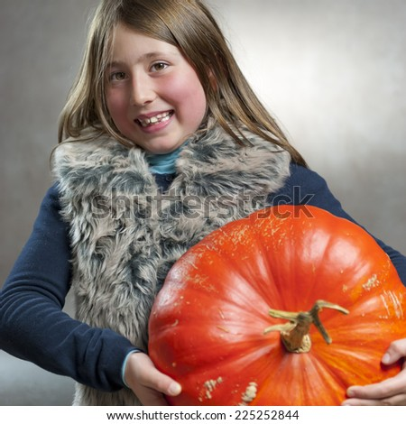 Closeup portrait of little girl posing with a big orange pumpkin. Halloween theme. Studio shoot after freshly harvest in autumn. Color image - stock photo