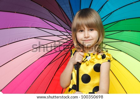 Closeup portrait of little girl standing under colorful umbrella - stock photo
