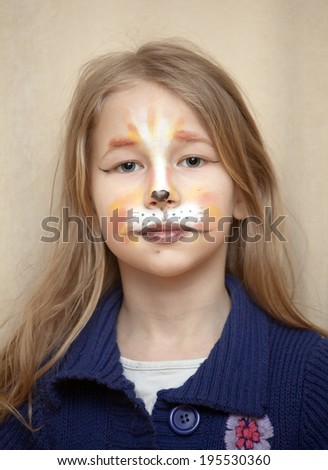 closeup portrait of little girl with cat painting makeup on the face looking at camera - stock photo