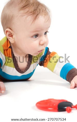 Closeup portrait of lying cute baby boy in multicolored striped clothes - stock photo