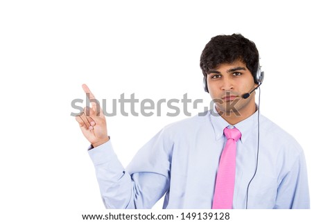 Closeup portrait of male customer service representative or call centre worker or operator or support staff speaking with head set, isolated on white background and pointing to copy space - stock photo