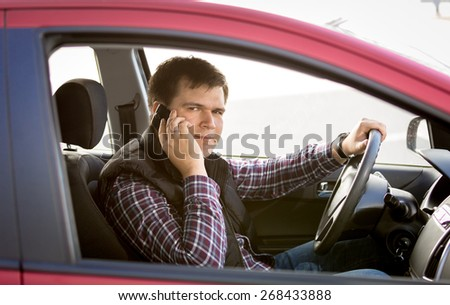 Closeup portrait of male driver talking by phone while driving a car - stock photo