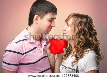 Closeup portrait of man and woman looking at each other and holding red heart between them
