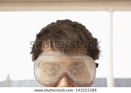 Closeup portrait of man wearing protective eyegoggles - stock photo