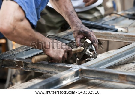 Closeup portrait of man working on still doors with hammer - stock photo