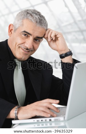 Closeup portrait of mature businessman sitting at desk, using laptop computer, smiling.