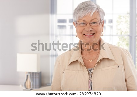 Closeup portrait of mature woman smiling happy, looking at camera. - stock photo