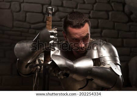 Closeup portrait of medieval knight looking down and kneeling with sword on a dark stonewall background