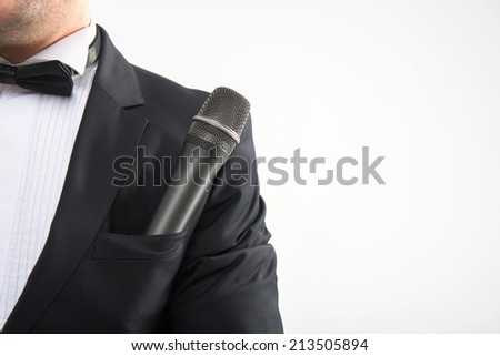 Closeup portrait of microphone sticking out from tuxedo pocket, neck with bowtie, isolated on white