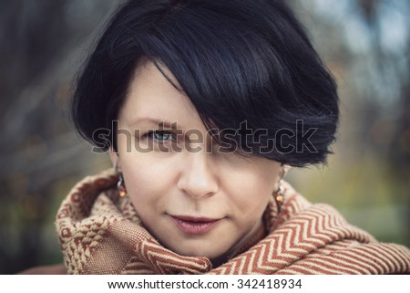 Closeup portrait of middle aged white caucasian brunette woman with short hair, green eyes with yellow orange woolen scarf on her neck  looking camera outside in autumn  park, stylish fashion concept - stock photo