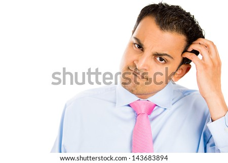 Closeup portrait of nerdy, idiot, dork, fool scratching his head in deep thought, puzzled, looking at you, daydreaming, isolated on white background with copy space to left - stock photo