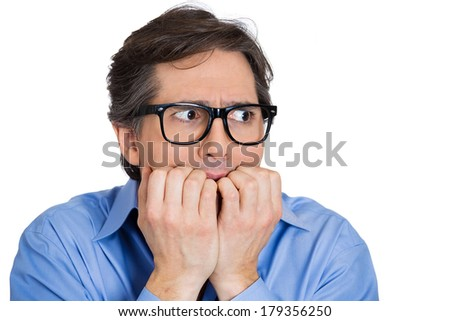 Closeup portrait of nervous stressed young nerdy guy, funny man with eyeglasses biting fingernails looking anxiously craving something isolated on white background. Negative emotion expression feeling