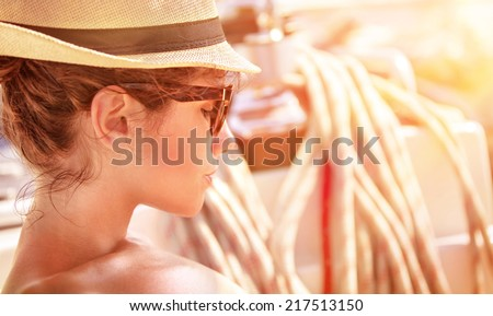 Closeup portrait of of cute female relaxing on the yacht in mild sunset light, side view of attractive woman wearing stylish hat and sunglasses, summer vacation concept - stock photo