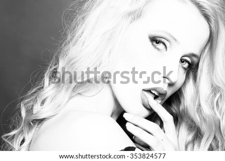 Closeup portrait of one attractive flirtatious sexy passionate blonde woman with long curly hair in studio with bare shoulder and finger in mouth looking forward black and white, horizontal picture