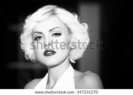 Closeup portrait of one attractive sensual dreaming young retro woman with blonde hair bright lips in dress in monroe style indoor on light background black and white, horizontal picture